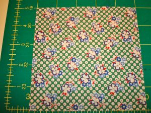 "Single charm square laid out on cutting mat - size is 5""x5"""